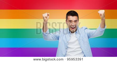 gesture, emotions, homophobia and people concept - angry gay man with raised hands over rainbow flag stripes background