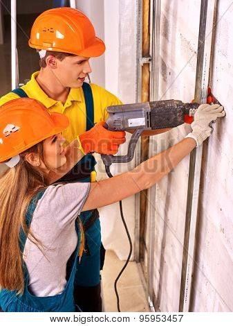 Happy woman working  and man in builder uniform indoor.