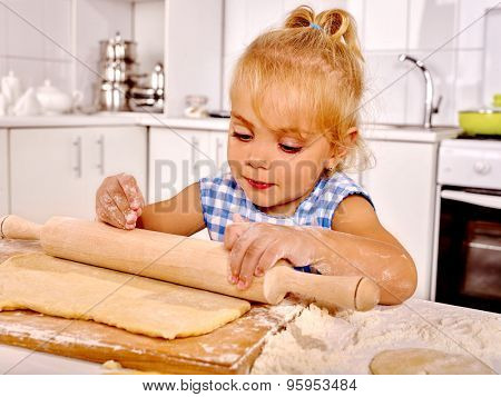 Child little girl with rolling-pin preparing dough at kitchen.