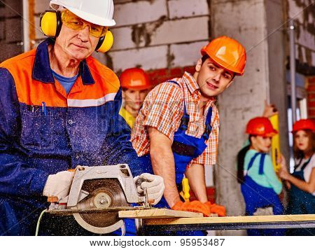 Happy group people  and old man builder with circular saw. Brick wall in background.