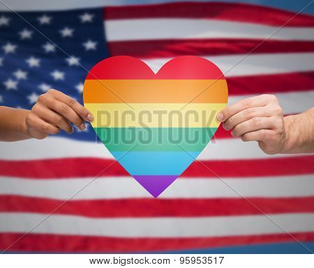 people, gay pride, gesture and homosexual concept - close up of couple hands holding rainbow heart shape over american flag background