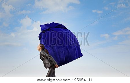 Businesswoman carrying big heavy bag on back
