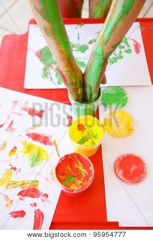 Child Dipping Fingers In Washable Finger Paints