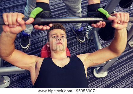 sport, fitness, equipment, lifestyle and people concept - men doing barbell bench press in gym with personal trainer or friend
