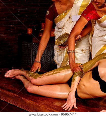 Young woman having legs and feet Ayurveda spa massage.