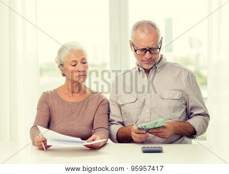 family, savings, age and people concept - senior couple with papers, money and calculator at home