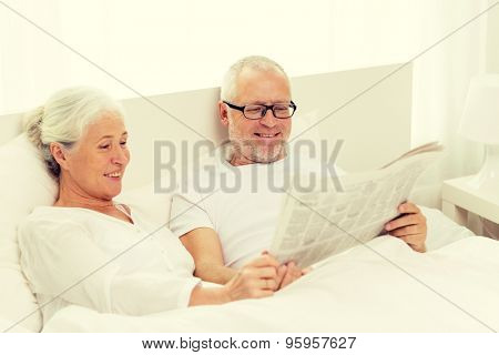 family, bedtime, resting, age and people concept - happy senior coupler with newspaper lying in bad at home