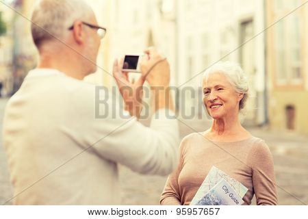age, tourism, travel, technology and people concept - senior couple with map and camera photographing on street