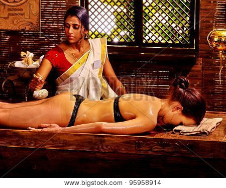 Woman having Ayurveda buttocks massage with pouch of rice.