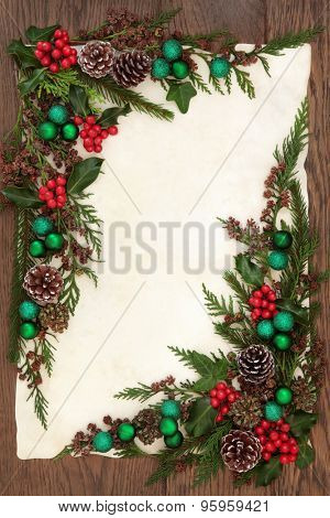 Christmas background border with green bauble decorations, holly, ivy and winter greenery on old parchment paper over oak.