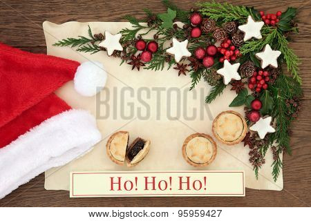 Christmas blank letter to santa claus with ho ho ho sign, hat, mince pies, gingerbread biscuits, holly, red baubles and winter greenery on parchment paper over oak background.