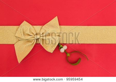 Gift box wrapping with gold ribbon and bow with mistletoe over red background.