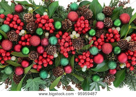 Christmas flora with red and green bauble decorations, holly, ivy, mistletoe, blue spruce fir and cedar cypress greenery.