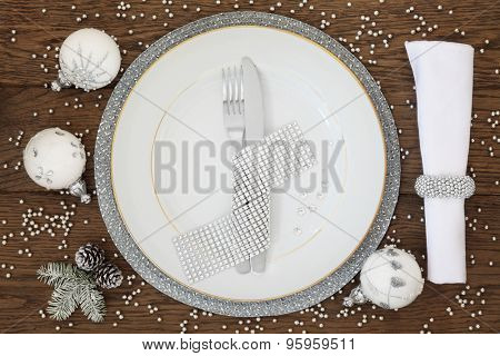 Christmas holiday dinner place setting with plate, napkin, cutlery, sparkling bauble decorations over oak table background.