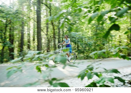 Young woman riding bicycle on summer weekend