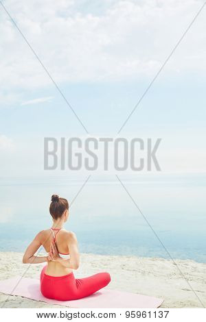 Young woman with crossed legs and arms behind back sitting on sand by water