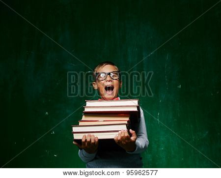 Ecstatic schoolboy in eyeglasses holding books