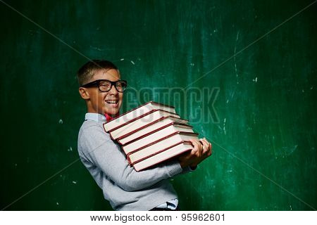 Cheerful schoolkid with stack of books looking at camera