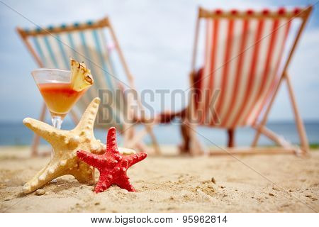 Two sea stars and tropical cocktail on sandy beach