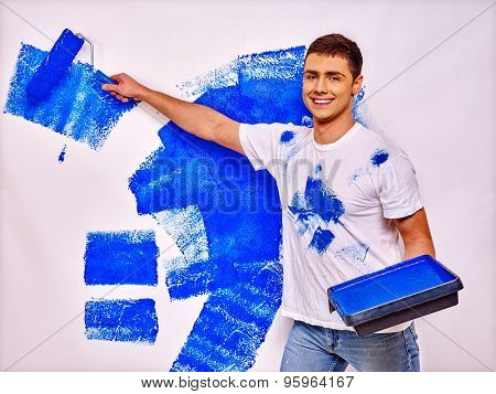 Happy man and messy clothes paint wall at home.
