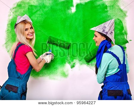 Happy two women in peper hat paint wall at home.