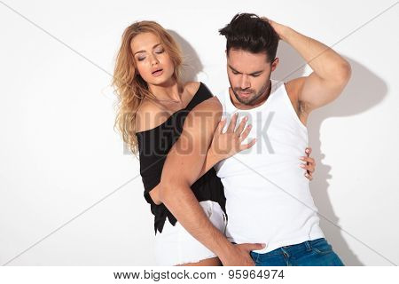 Sexy blonde woman holding her lover while he is fixing his hair, both looking down.