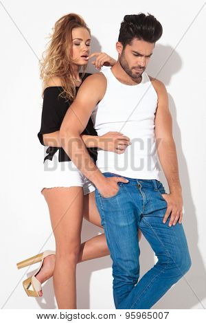 Blonde woman holding one leg up while her lover is looking down with one hand in his pocket.