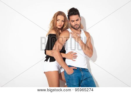 Young casual man holding his hand on his chest while his girfriend is embracing his from behind.
