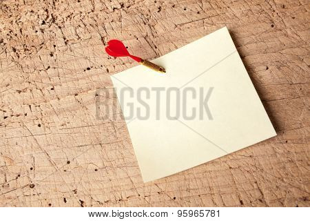 Red dart in an empty or blank notepad on a vintage wooden board