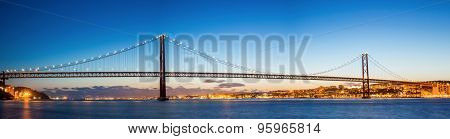 Panorama of Lisbon cityscape with 25 de Abril suspension Bridge, Portugal at dusk