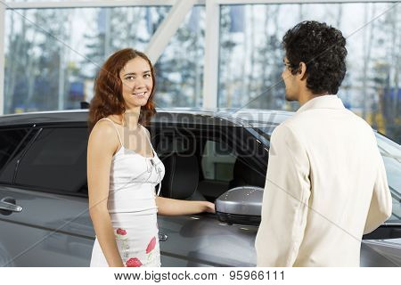 Young man dealer in auto salon presenting car to customer