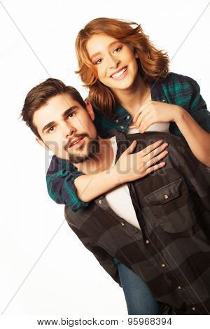 emotional, happiness and people concept: Happy loving couple. Young man piggybacking his girlfriend. Studio shot over white background.Special Fashionable toning photos.