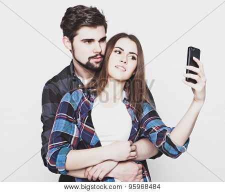 tehnology, internet, emotional  and people concept: Capturing happy moments together. Happy young loving couple making selfie and smiling while standing