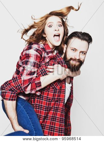 life style, happiness and people concept: Happy loving couple. Young man piggybacking his girlfriend. Studio shot over white background.Special Fashionable toning photos.