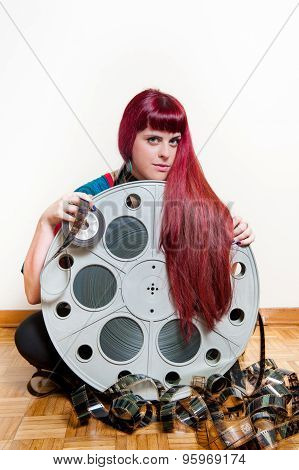 Young Woman Smile Behind Big Movie Cinema Reel With Filmstrip Roll