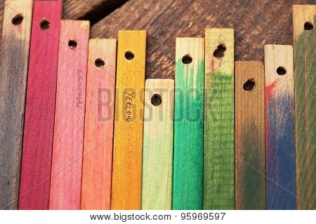 Colorful wood stain color test wood samples, on rough wood.