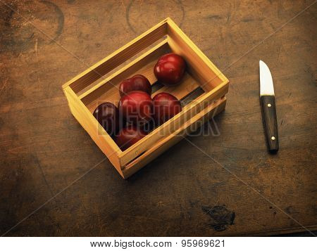 Fresh harvested plums, very ripe. In a small wooden crate. Plums on a old wooden table.