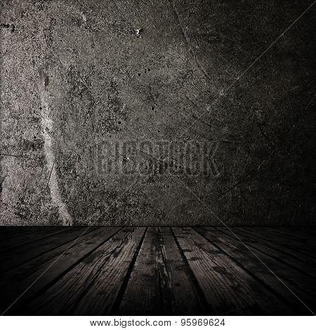 Dark room with stone wall and grungy old wooden floor.