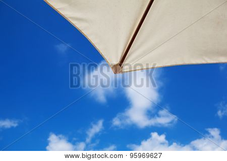 Summer sky. Sunny summer blue sky seen from under a beach parasol.