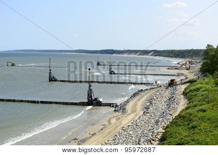 USTKA - JULY 07: Workers build a breakwater to facilitate the construction of the beach on 7 July 2015 in Ustka, Poland.