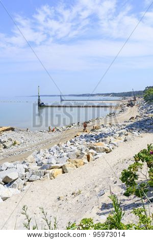 USTKA - JULY 04: Workers build a breakwater to facilitate the construction of the beach on 4 July 2015 in Ustka, Poland.