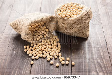 Soybean In A Bag On Wooden Background.