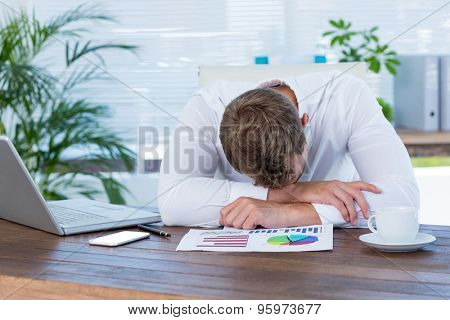 Exhausted businessman sleeping on the desk in the office