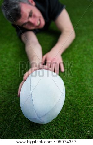 A determined rugby player scoring a try