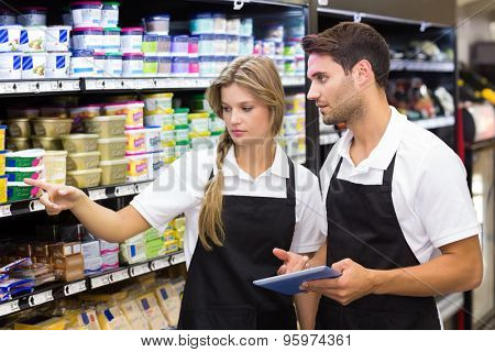 Serious colleagues showing and using a digital tablet at supermarket