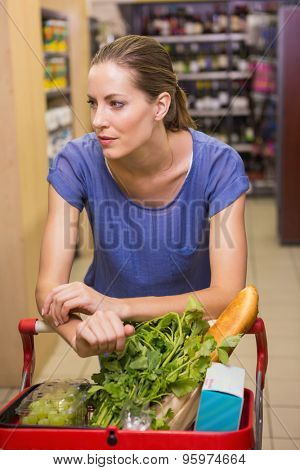 Thoughtful pretty woman pushing trolley in supermarket
