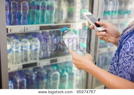 Woman comparing the price of a bottle of water with her phone at the supermarket