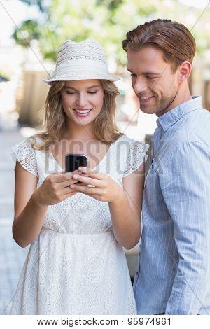 A standing cute couple sending a text message