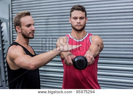 Trainer supervising a muscular man lifting a kettle bell
