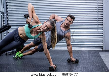 Portrait of a muscular couple doing side plank while lifting weights